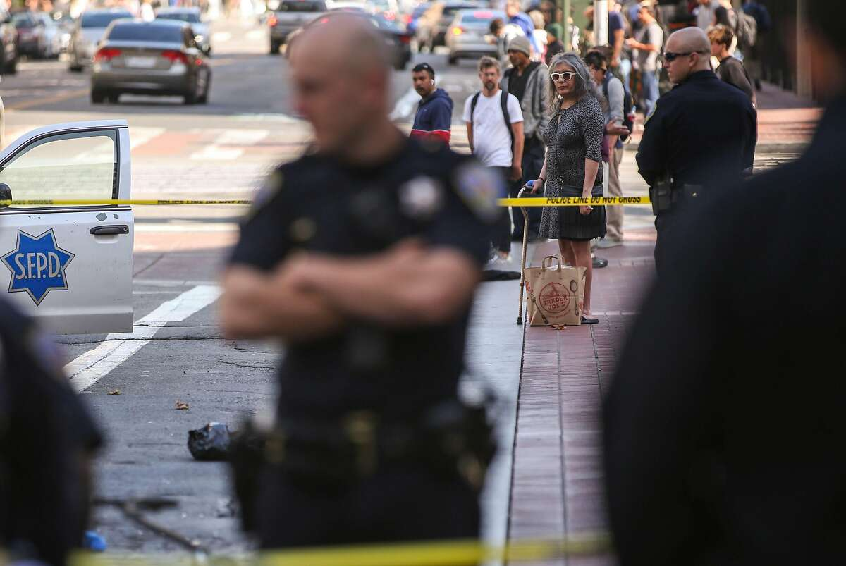 Onlookers watch San Francisco Police Officers near Market Street and 5th Street where a police officer allegedly shot a dog Wednesday, July 31, 2019, in San Francisco, Calif.