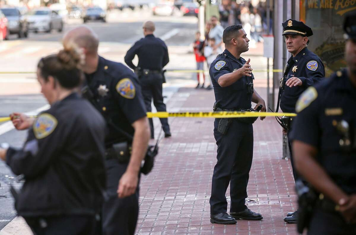 San Francisco Police Officers confer on the scene near Market Street and 5th Street where a police officer allegedly shot a dog Wednesday, July 31, 2019, in San Francisco, Calif.