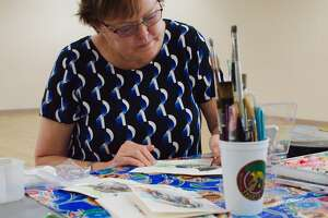 Terri Cook works on a painting during watercolor class Wednesday, Jul. 31 at the League City Recreation Center.