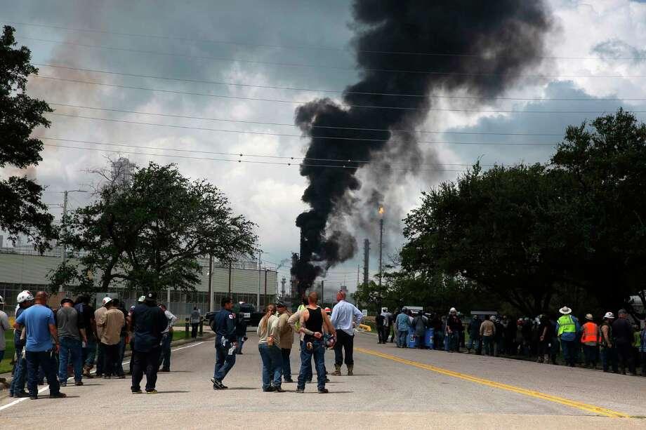 Trabajadores evacuados de Exxon Mobil toman un descanso u observan el incendio de la entrada a la planta Baytown Olefins el miércoles 31 de julio de 2019 en Bayton, Texas. Photo: Yi-Chin Lee /Associated Press / Houston Chronicle