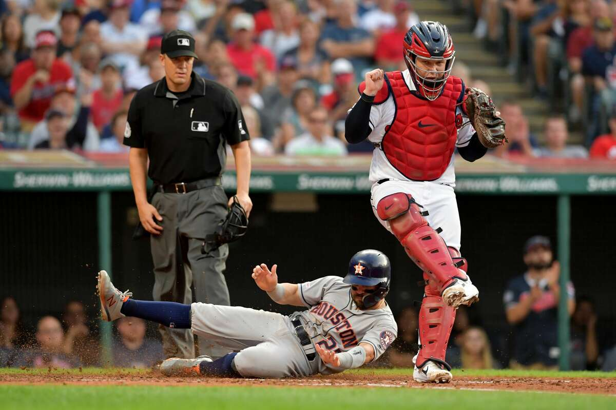CLEVELAND, OHIO - JULY 31: Catcher Roberto Perez #55 of the Cleveland Indians hops out of the way after forcing out Jose Altuve #27 of the Houston Astros at the plate in the third inning at Progressive Field on July 31, 2019 in Cleveland, Ohio. (Photo by Jason Miller/Getty Images)