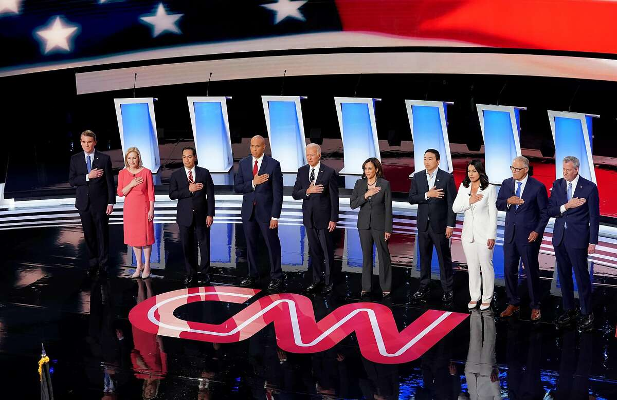 DETROIT, MICHIGAN - JULY 31: Democratic presidential candidates Sen. Michael Bennet (D-CO) (L-R), Sen. Kirsten Gillibrand (D-NY), former housing secretary Julian Castro, Sen. Cory Booker (D-NJ), former Vice President Joe Biden, Sen. Kamala Harris (D-CA) , former tech executive Andrew Yang, Rep. Tulsi Gabbard (D-HI), Washington Gov. Jay Inslee, and New York City Mayor Bill De Blasio take the stage at the Democratic Presidential Debate at the Fox Theatre July 31, 2019 in Detroit, Michigan. 20 Democratic presidential candidates were split into two groups of 10 to take part in the debate sponsored by CNN held over two nights at Detroits Fox Theatre. (Photo by Scott Olson/Getty Images)