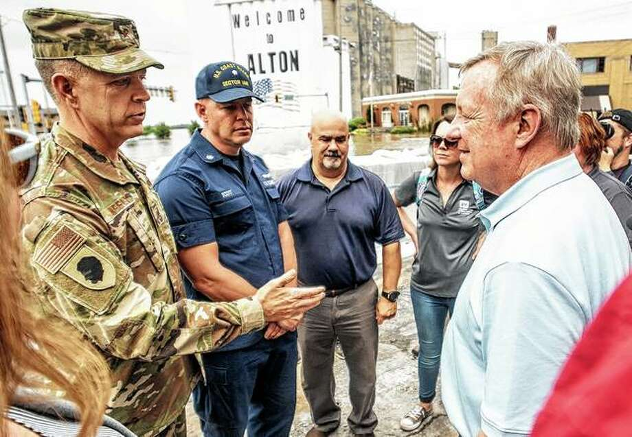 Brig. Gen. Richard Neely (from left), adjutant general of the Illinois National Guard, and Coast Guard Capt. Scott Stoermer, commander of the Upper Mississippi River sector, speak with U.S. Sen. Dick Durbin while surveying floodwaters in downtown Alton. Photo: Hearst Illinois