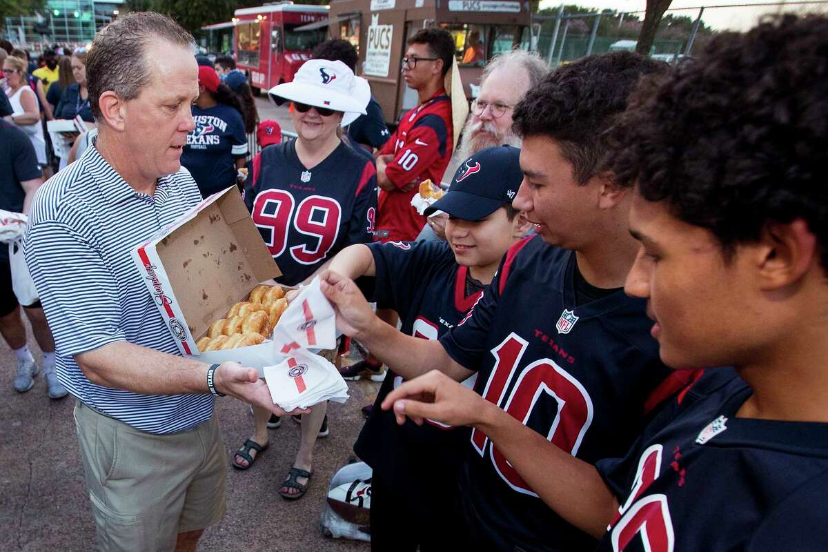 Houston Texans president Jamey Rootes hands out donuts to the early-arriving fans in line to watch the Texans first open practice of training camp at the Methodist Training Center on Thursday, Aug. 1, 2019, in Houston.