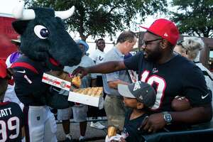 Houston Texans mascot Toro hands out donuts to the early-arriving fans in line to watch the Texans first open practice of training camp at the Methodist Training Center on Thursday, Aug. 1, 2019, in Houston.