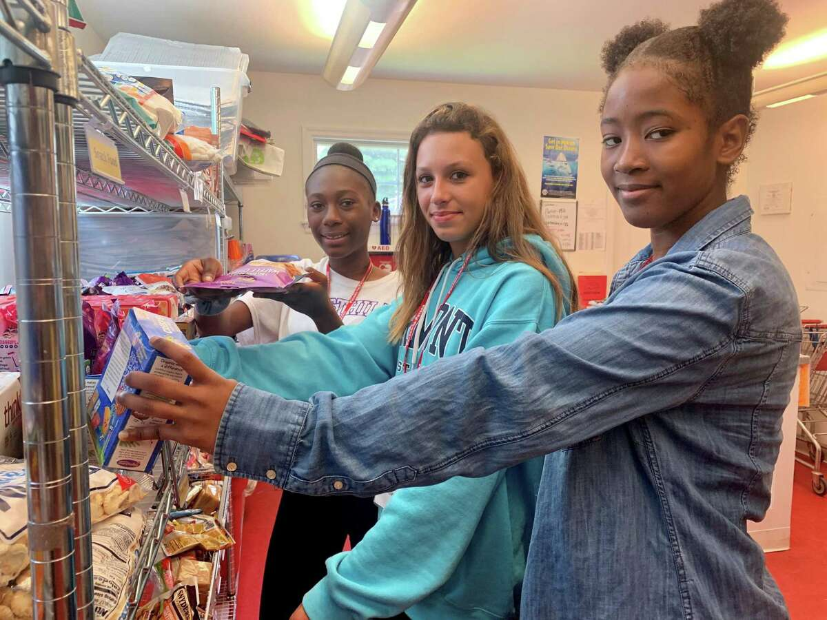 Behanka Adonis, Jasmine Shtufaj, and Naika Sylvain are sorting food in Person-To-Person's food pantry. They are volunteers in the summer youth group program.
