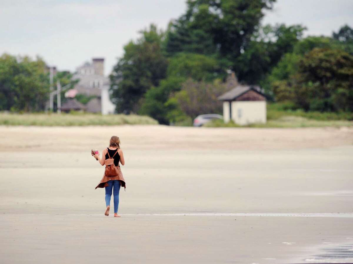 On a cloudy and cool second to last day of summer, a woman walking barefoot has the beach to herself at Greenwich Point, Conn., Friday, Sept. 21, 2018.