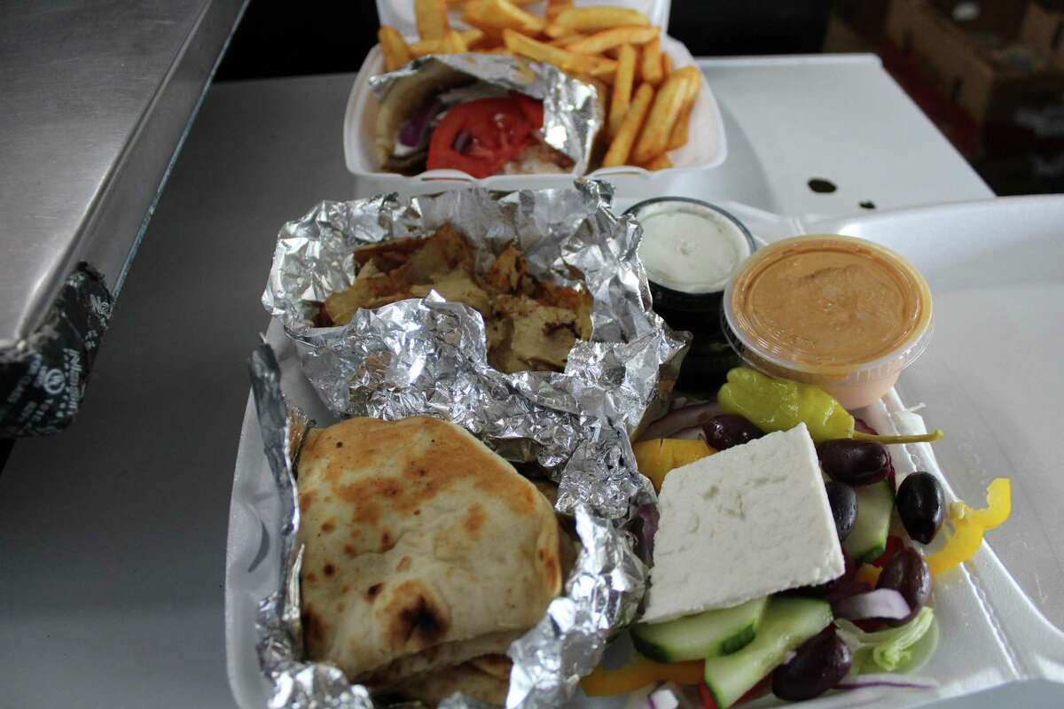 Taste of Greek makes traditional Greek cuisine such as a lamb gyro with fries, that's shown in the back, and a chicken gryo plate that 's shown in the front.