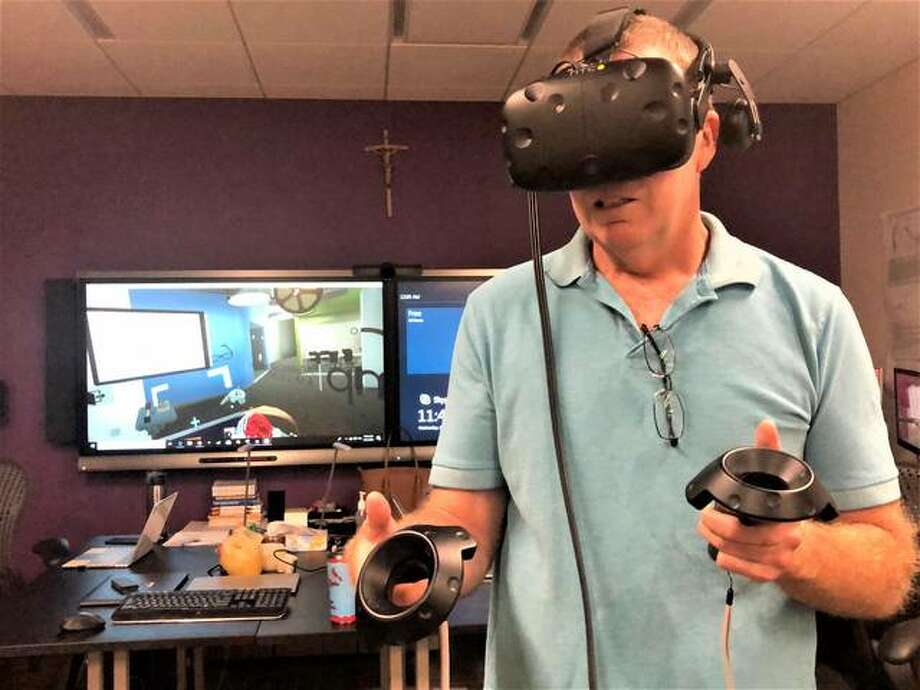 Marquette High School Science Department Chair John Walters dons virtual reality headset and controllers on Thursday to experience the immersive technology used to train students at the Jump Trading Simulation and Education Center in Peoria.