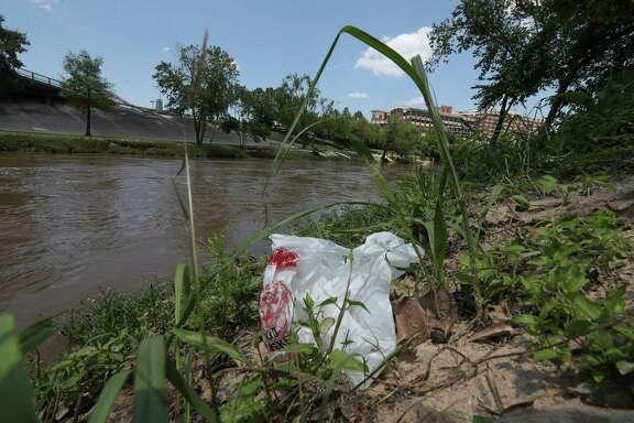 Plastic waste is visible along Buffalo Bayou.