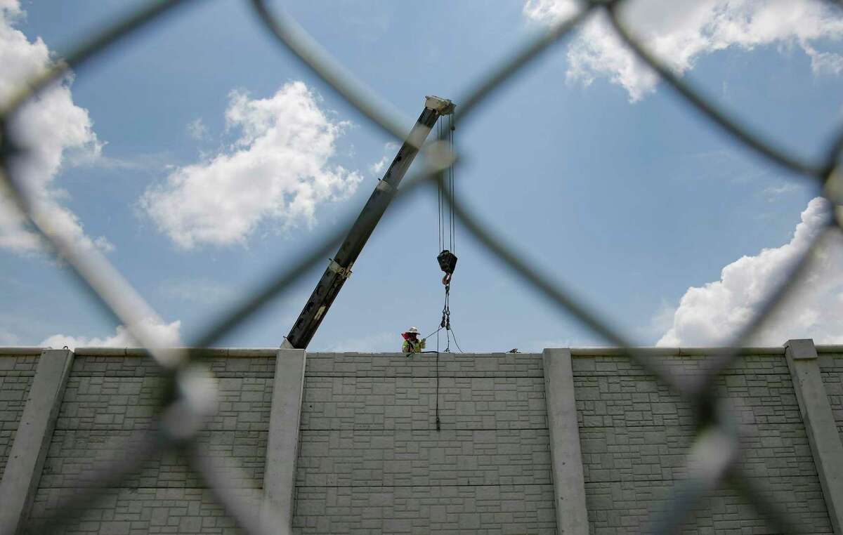 A construction worker puts the finishing touches on a wall between Interstate 69 and a neighborhood in Houston on July 11, 2019.