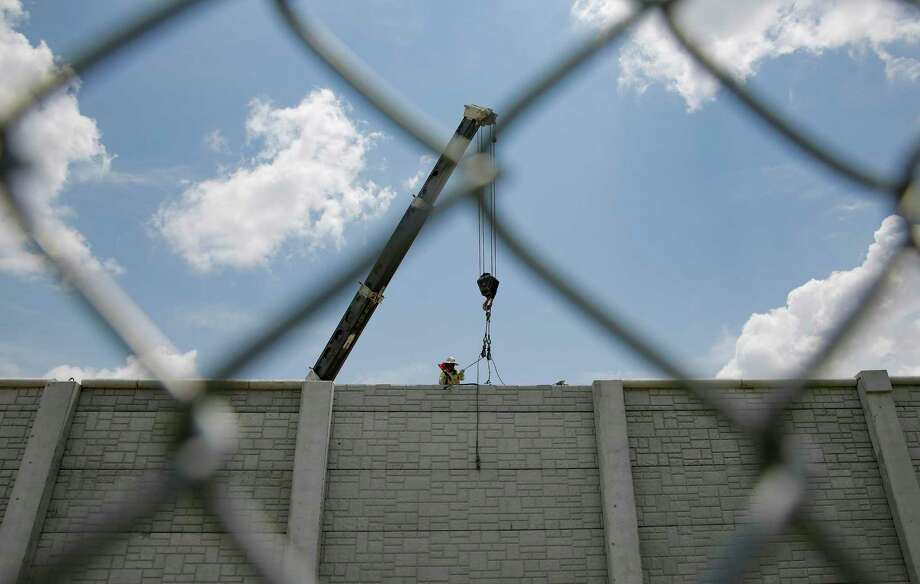 A construction worker puts the finishing touches on a wall between Interstate 69 and a neighborhood west of Post Oak on July 11, 2019. Photo: Elizabeth Conley, Houston Chronicle / Staff Photographer / © 2018 Houston Chronicle