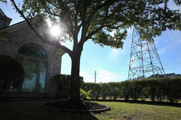 A CenterPoint Energy electricity tower stands outside the Pearland home of Eboni Hollier. The regulated public utility suffered a major defeat Thursday when it agreed to a deal that will sharply reduce its requested rate hike.