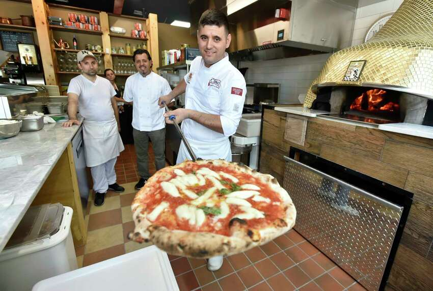 New Haven, Connecticut - Thursday, August 1, 2019: Gazmir Zenelli, right, with his brother Jeshar Zeneli, center, co-owners with their brother Aleko Zeneli (not in photo), and employee and pizza maker Marco Mazzomi, left, shows off his Queen Margherita pizza cooked in the wood-fired oven before the grand opening of Zeneli's Pizzeria & Cucina Napoletana on Wooster Street in New Haven Thursday. The restaurant fare offers New York City award winning pizza and pasta among other menu items. The Zaneli brothers immigrated from Albania, to Italy, then Brooklyn and have followed their dreams by landing on New Haven's Wooster Street, arguably the pizza capital of the world.