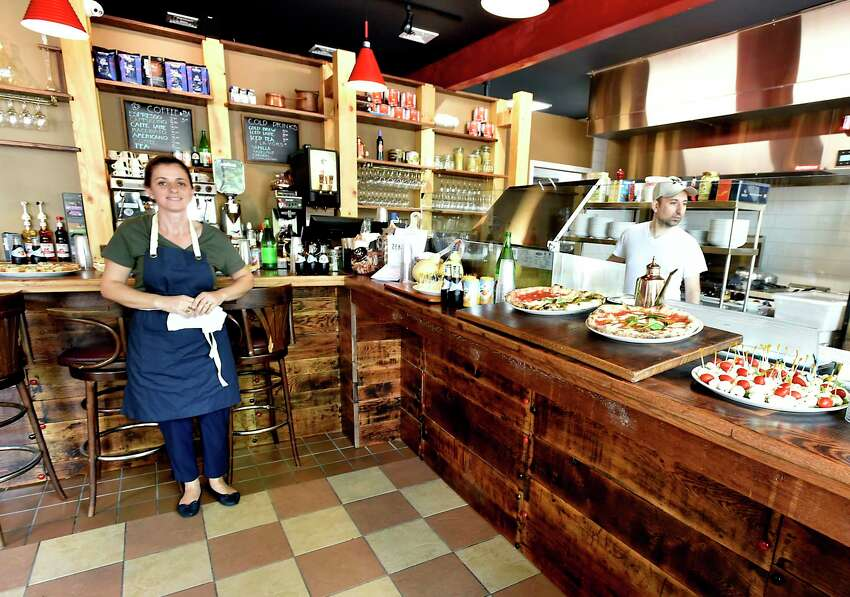 New Haven, Connecticut - Thursday, August 1, 2019: Waiting for guides employees of Zeneli's Pizzeria & Cucina Napoletana on Wooster Street in New Haven Thursday wait for guests to enter the front end of the pizzeria restaurant to sample some of their food. The restaurant fare offers New York City award winning pizza and pasta among other menu items. The Zaneli brothers immigrated from Albania, to Italy, then Brooklyn and have followed their dreams by landing on New Haven's Wooster Street, arguably the pizza capital of the world.