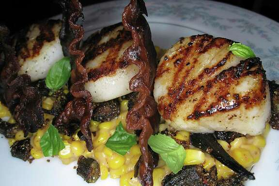 Grilled scallops come with creamed corn, okra and fried pieces of country ham at Kindling Texas Kitchen.