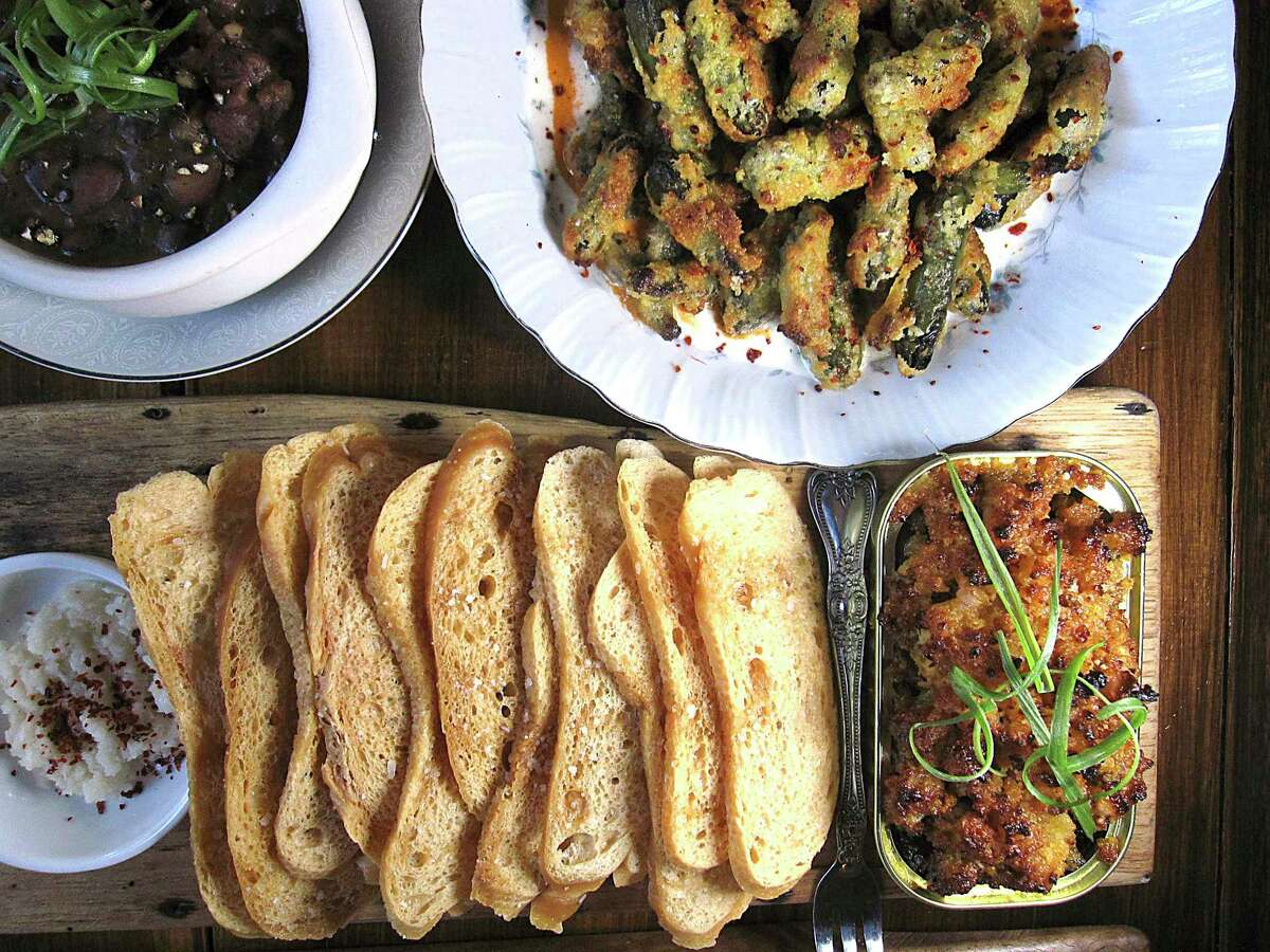 Appetizers include pinto beans with bacon and rib-eye, crispy fried pickles with roasted pepper sauce and tinned smoked oysters with Parmesan stuffing and horseradish at Kindling Texas Kitchen.