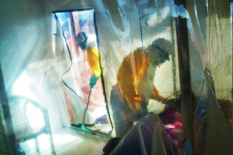 Health workers wearing protective suits tend to to an Ebola victim kept in an isolation tent in Beni, Democratic Republic of Congo, on Saturday, July 13, 2019. The Congolese health ministry is confirming the country's first Ebola case in the provincial capital of 2 million, Goma, some 360 kilometers (225 miles) south of Beni. More than 1,600 people in eastern Congo have died as the virus has spread in areas too dangerous for health teams to access. (AP Photo/Jerome Delay)