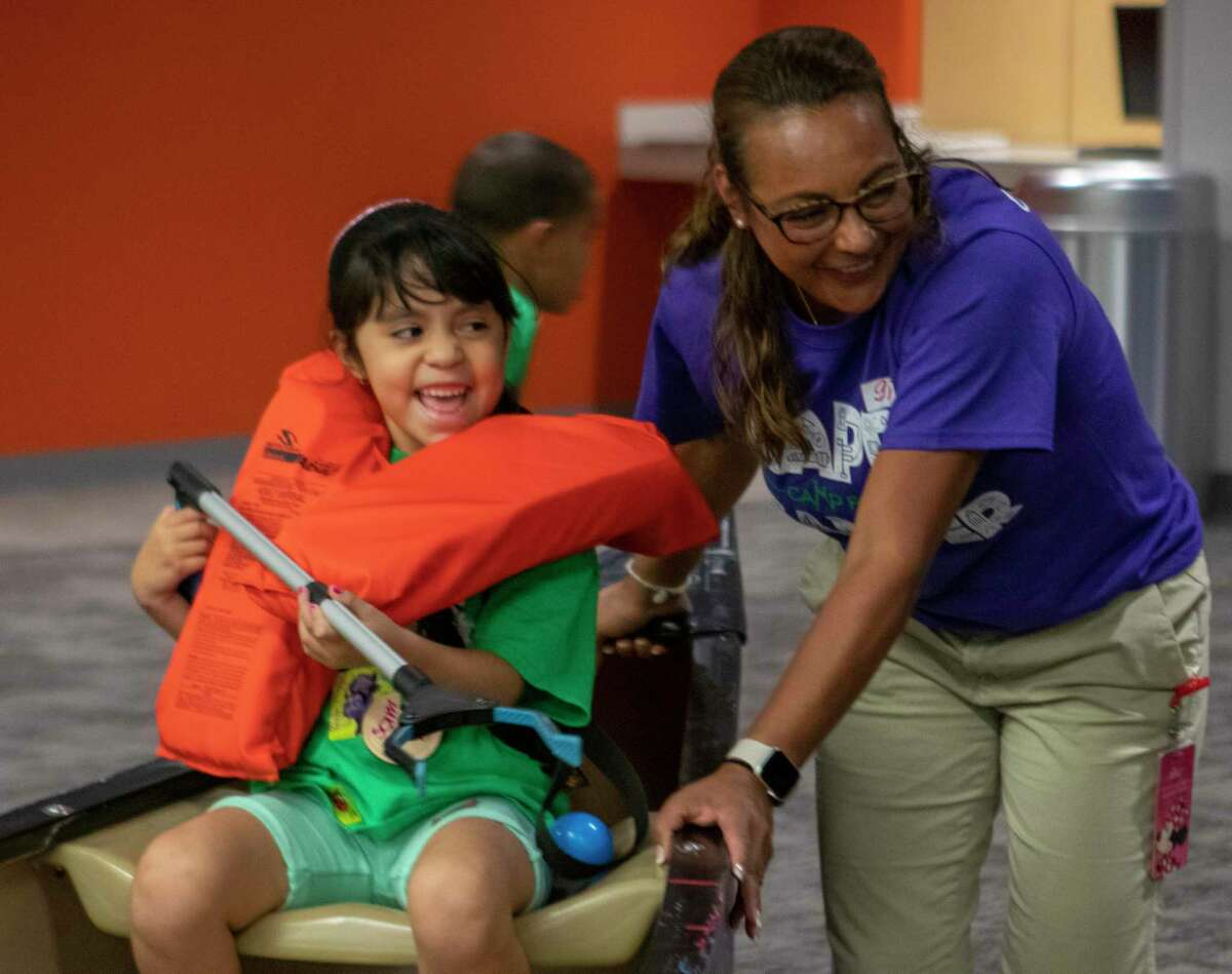 Samantha Torres laughs as she is pushed around in a canoe during a game of Battleship for a Camp For All 2U event Wednesday, July 31, 2019 at Texas Children's Hospital The Woodlands.