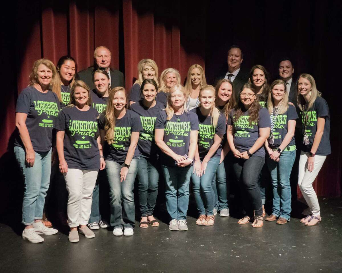 Teachers and administrators with Neill Elementary in Harvest Green pose with Harvest Green Marketing Director Haley Peck, back row third from right, and Harvest Green General Manager Jerry Ulke, back row, second from right, after learning of a sizeable donation to the Fort Bend Education Foundation.