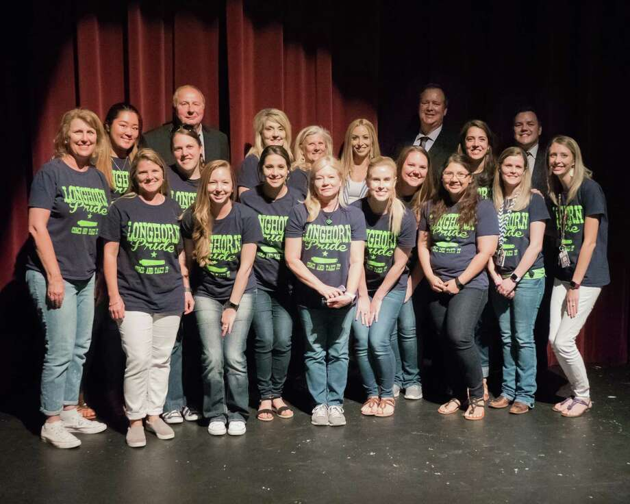 Teachers and administrators with Neill Elementary in Harvest Green pose with Harvest Green Marketing Director Haley Peck, back row third from right, and Harvest Green General Manager Jerry Ulke, back row, second from right, after learning of a sizeable donation to the Fort Bend Education Foundation. Photo: Courtesy Photo