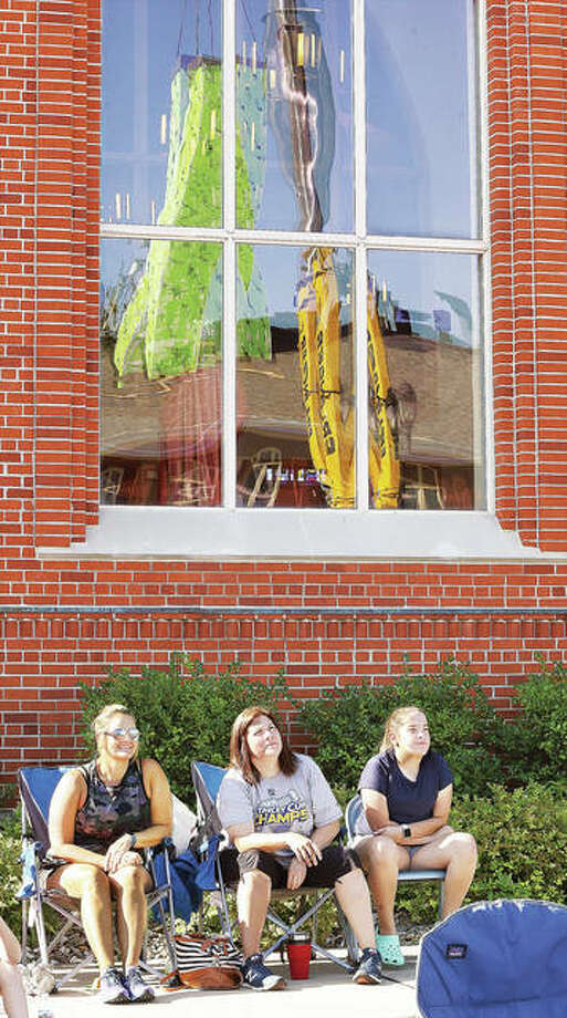 Three parishioners at St. Boniface Catholic Church in Edwardsville on Thursday morning watch a large crane lift a green-clad, three-story elevator shaft that can be seen in the church window behind them. The pre-fabricated shaft was lowered through a hole cut in the roof of St. Boniface School as part of a large renovation project to make the facility ADA compliant. About 50 people, mostly parishioners, turned out to watch the several-hour-long project. Additional photos are online at www.thetelegraph.com.
