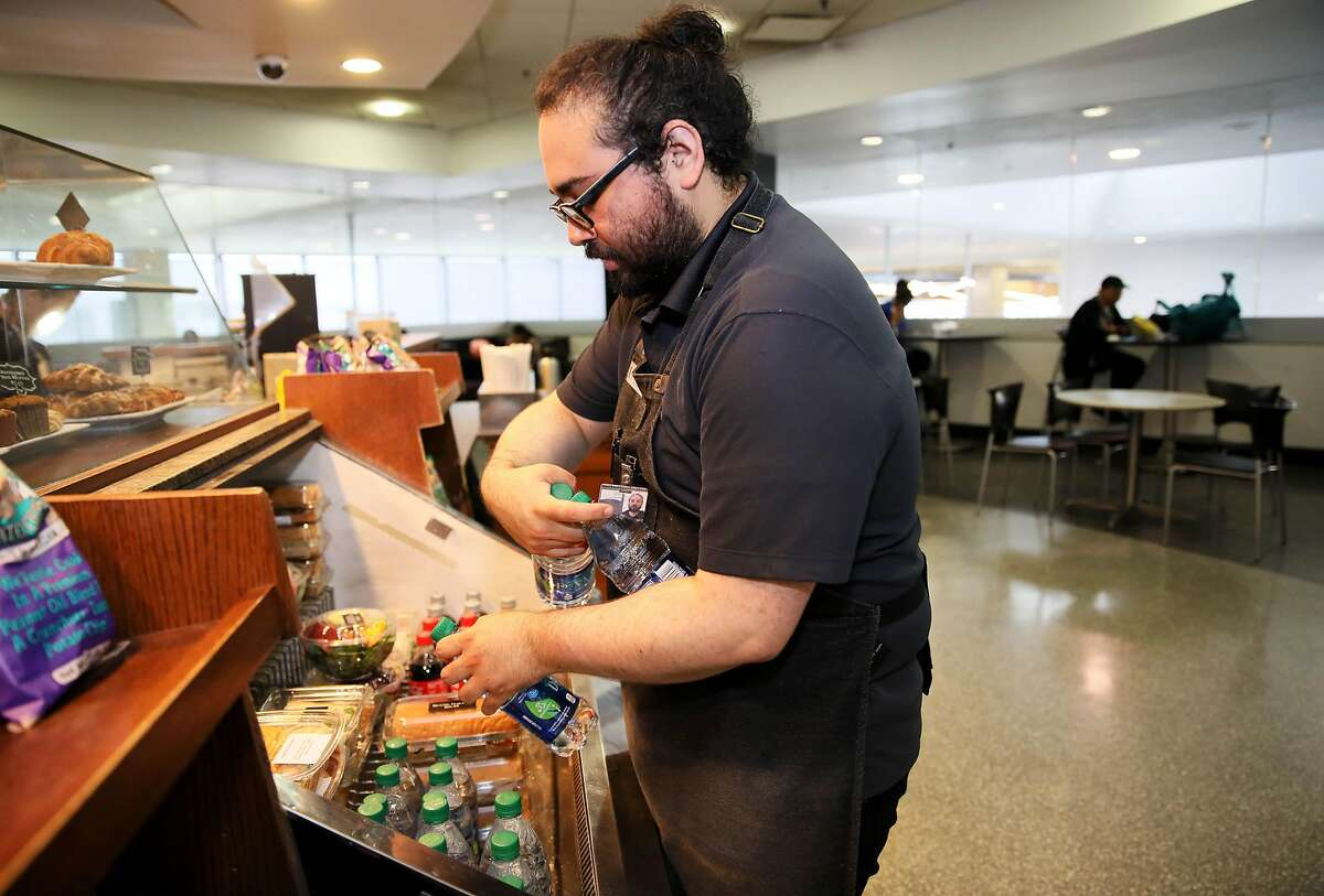 Peet's Coffee and Tea employee Dugaldo Avalos stocks plastic bottles of water in Terminal 3 at the San Francisco International Airport in San Francisco, Calif., on Thursday, August 1, 2019. The airport will require vendors to cease selling water in plastic bottles beginning August 20, replacing them with glass bottles or aluminum cans.