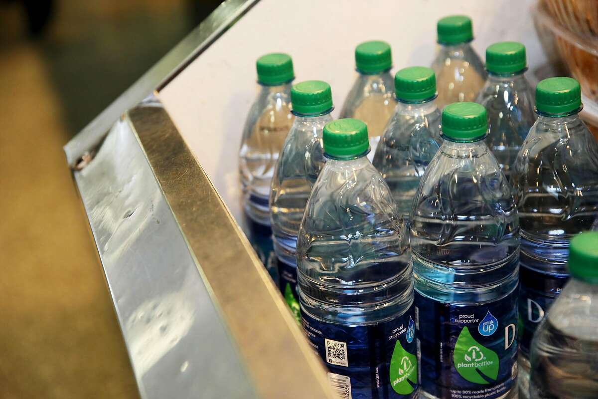Plastic bottles of water sit in a refrigerator at Peet's Coffee and Tea in Terminal 3 at the San Francisco International Airport in San Francisco, Calif., on Thursday, August 1, 2019. The airport will require vendors to cease selling water in plastic bottles beginning August 20, replacing them with glass bottles or aluminum cans.