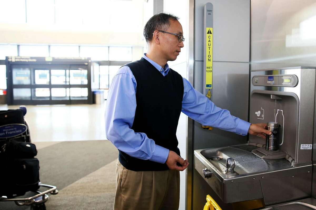 Traveler Jiming Bao, of Houston, Texas, refills his water bottle at a hydration station in Terminal 3 at the San Francisco International Airport in San Francisco, Calif., on Thursday, August 1, 2019. The airport will require vendors to cease selling water in plastic bottles beginning August 20, replacing them with glass bottles or aluminum cans.