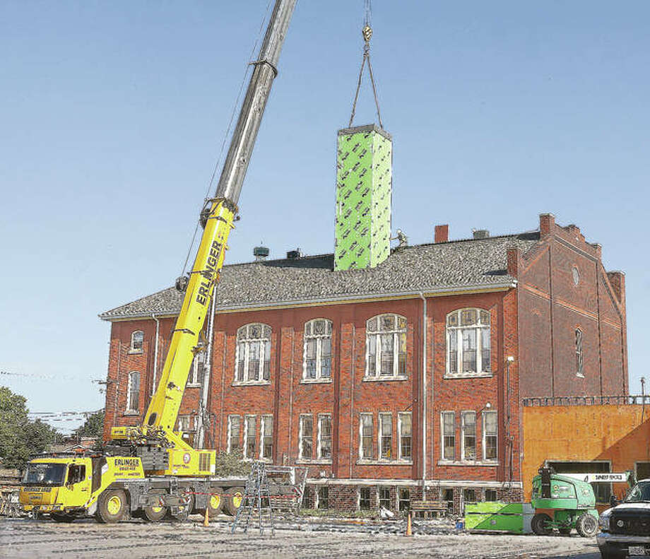 The elevator shaft starts its descent through the hole in the parish school on its way to the basement footings where it reportedly had less than an inch of clearance on each side in order to fit correctly into place. Photo: John Badman | Hearst Illinois