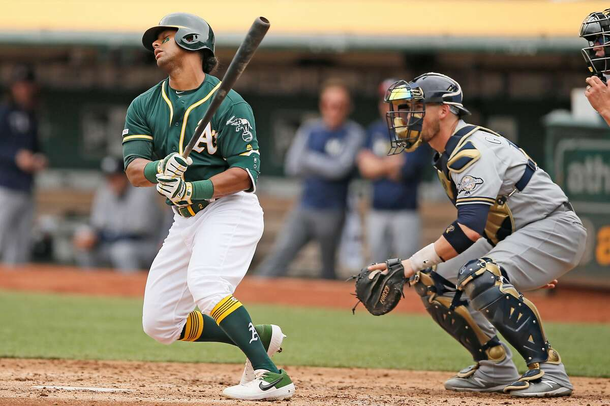 Oakland Athletics left fielder Khris Davis (2) runs to first base after hitting a grounder for an out during the fourth inning of an MLB game against the Milwaukee Brewers at the Oakland-Alameda County Coliseum, Thursday, Aug. 1, 2019, in Oakland, Calif.