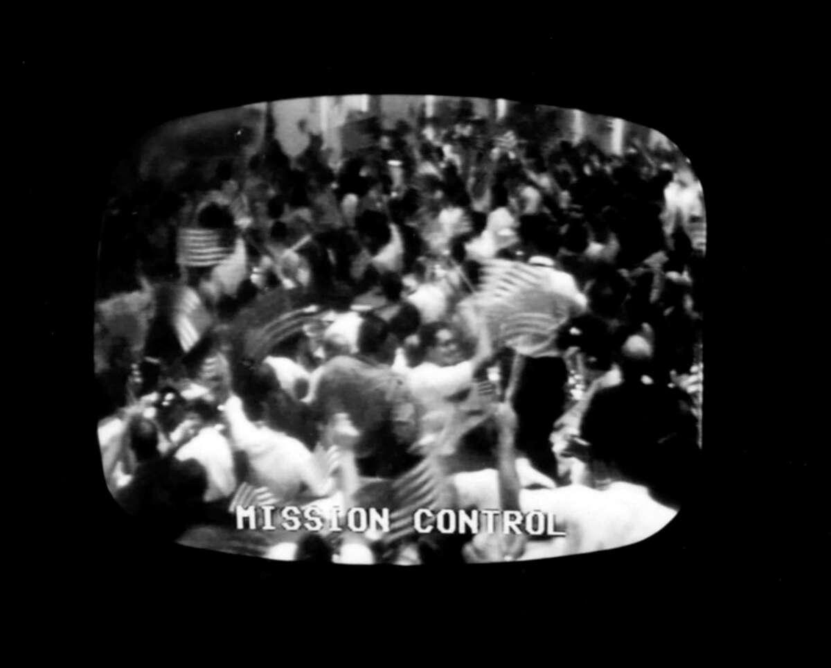 """Mission Control in Houston erupts in flag-waving celebration after the safe return to Earth of the Apollo 11 astronauts on July 24, 1969. That day, every American was simply an American - all differences were set aside while everyone celebrated what """"we"""" accomplished."""