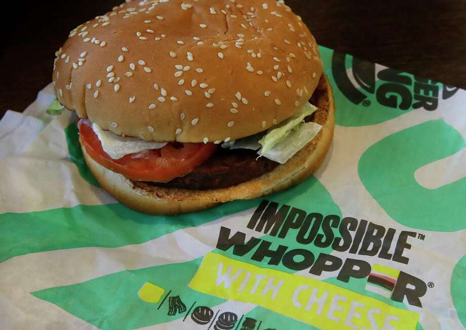 In this Wednesday, July 31, 2019 photo, an Impossible Whopper burger is photographed at a Burger King restaurant in Alameda, Calif. Burger King will soon offer its Impossible Whopper plant-based burger nationwide. The chain said the soy-based burger, made by Impossible Foods, will be available for a limited time at its 7,000 U.S. stores starting next week. (AP Photo/Ben Margot) Photo: Ben Margot / Ben Margot / Associated Press / Copyright 2019 The Associated Press. All rights reserved.