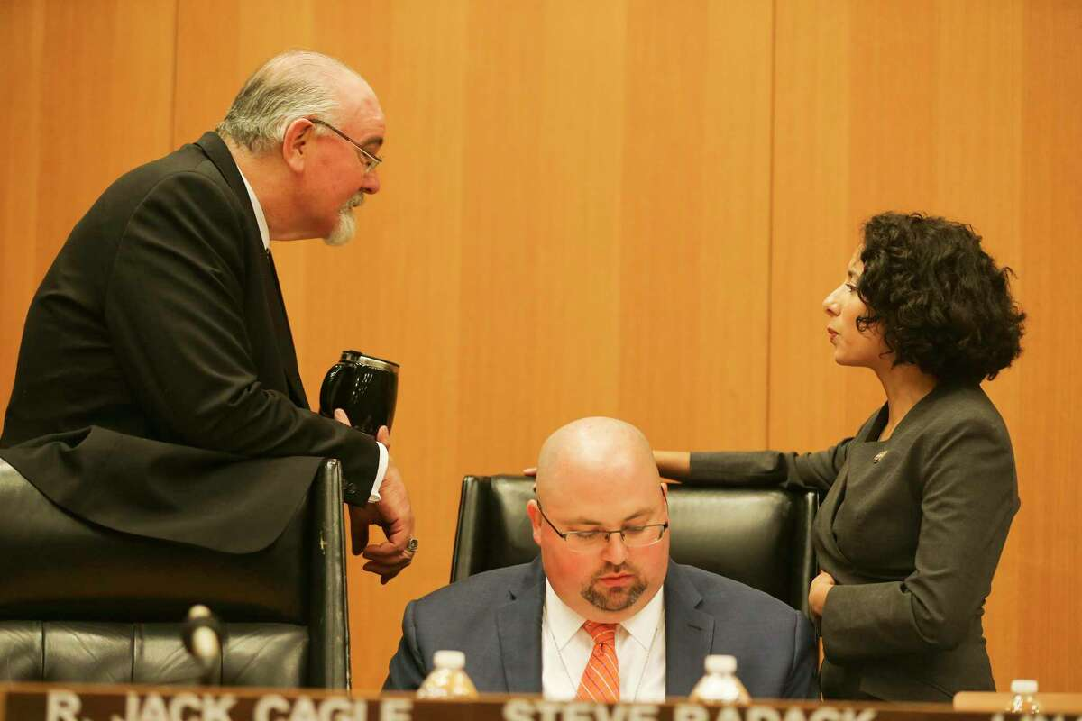 Newly-elected Harris County Judge Lina Hidalgo talks with Commissioner R. Jack Cagle over James Hastings, deputy Commissioners Court Clerk at her first Harris County Commissioners Court meeting since being elected on Tuesday, January 8, 2019 in Houston.