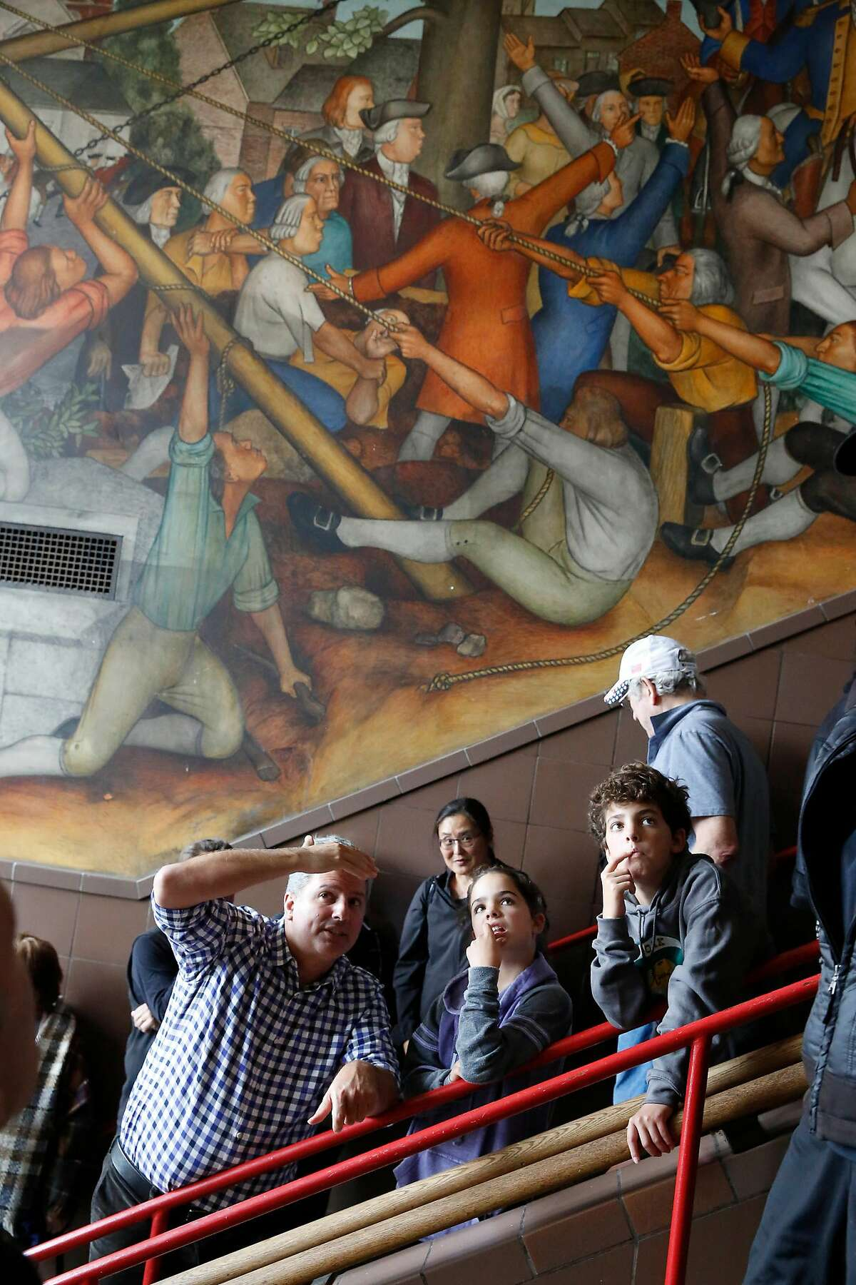 Charles Barr (l to r) talks with his children Phoebe Barr, 10 and Larry Barr, 12, all of San Francisco, as they look at a 1936 mural depicting the life of George Washington by San Francisco artist Victor Arnautoff at George Washington High School during a public viewing on Thursday, August 1, 2019 in San Francisco, Calif.