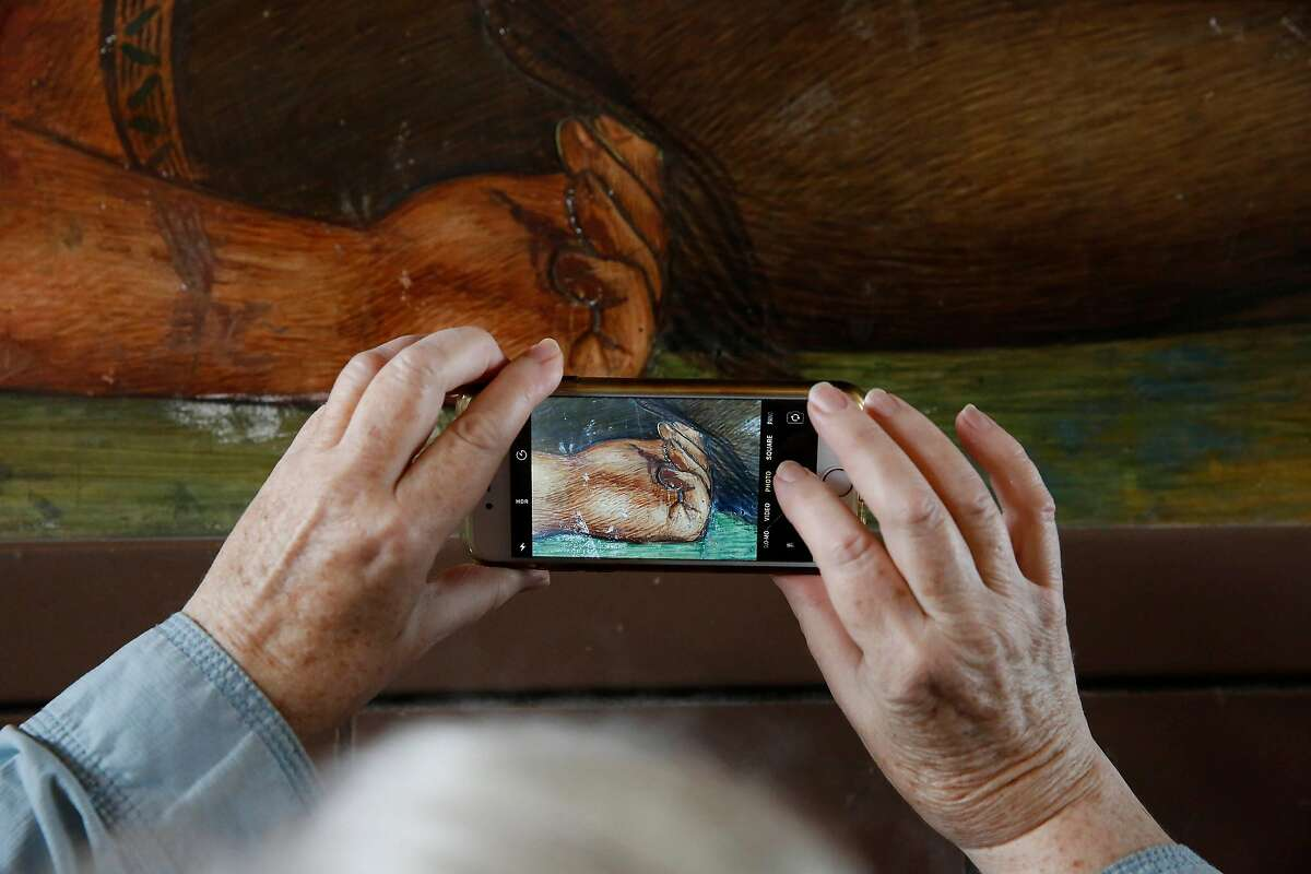 Kay Weinkam takes a close up photo of an Indian�s hand as she looks at a 1936 mural depicting the life of George Washington by San Francisco artist Victor Arnautoff at George Washington High School during a public viewing on Thursday, August 1, 2019 in San Francisco, Calif. Weinkam wondered why there was no concern over the partially naked woman on an alcove ceiling in the high school in the discussion of what to do with the mural.