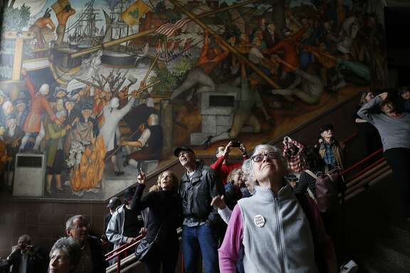 Vanya Akraboff (l to r) of Sausalito and Jeff Nemy discus the 1936 mural depicting the life of George Washington by San Francisco artist Victor Arnautoff at George Washington High School  as Jean Amos of San Francisco views it during a public viewing on Thursday, August 1, 2019  in San Francisco, Calif.