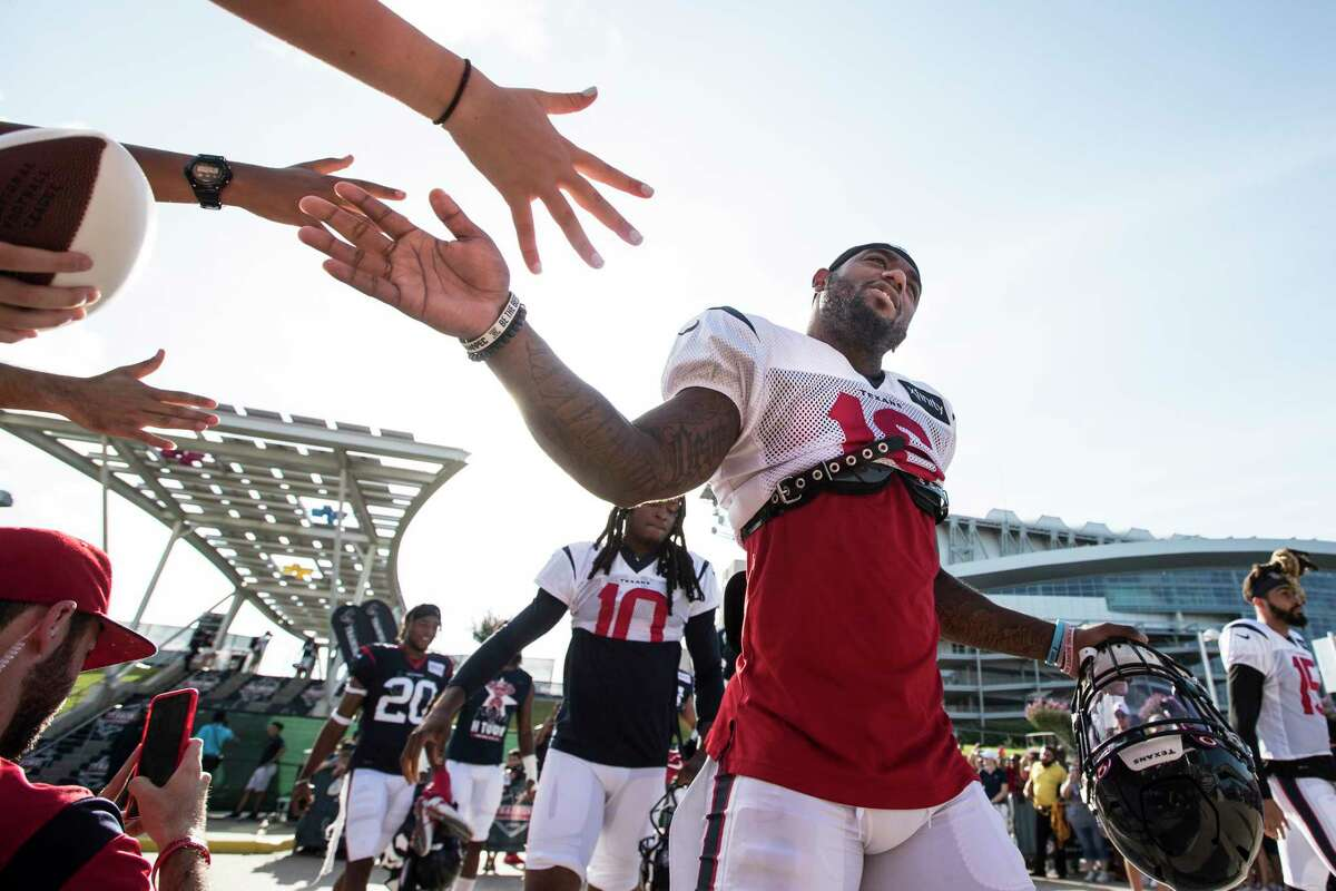 Houston Texans wide receiver Keke Coutee reaches out to slap hands with fans as he walks to practice during training camp at the Methodist Training Center on Thursday, Aug. 1, 2019, in Houston.