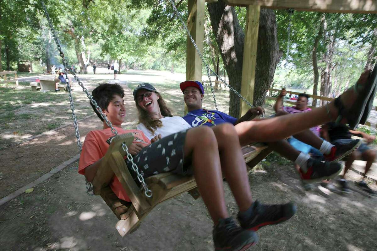 Camper Jayden Kaplan (from left), counselor Sophia Zaldivar and camper Julian Ramirez enjoy a leisurely moment on a swing beside the Guadalupe River at CAMP Camp on Thursday, Aug. 1, 2019. The camp offers children with special needs and disabilities a traditional summer camp experience and activities like swimming, canoeing, horseback riding and archery. The camp, is run by Children's Association for Maximum Potential (CAMP), which is celebrating its 40th anniversary. CAMP provides one-on-one supervision for each camper during their weeklong residential sessions. (Kin Man Hui/San Antonio Express-News)