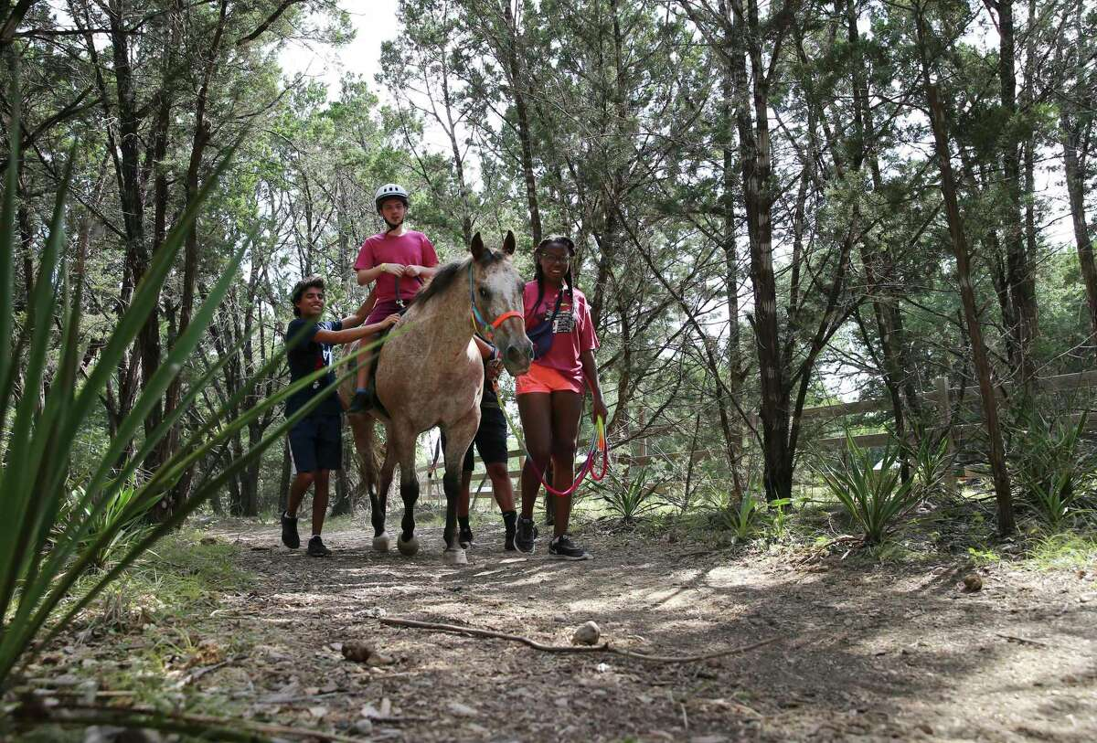 Camper Michael Kelley takes a ride on a horse named Spice with the help of Wynter Harris (right) and camp counselor Abraham Rivero (left) at CAMP Camp in Center Point, Texas on Thursday, Aug. 1, 2019. The camp offers children who are medically fragile or severely disabled a traditional summer camp experience with activities like swimming, canoeing, horseback riding and archery. The camp, which is celebrating its 40th anniversary, is run by Children's Association for Maximum Potential (CAMP) and provides one-on-one medical supervision for each camper during their weeklong residential sessions. (Kin Man Hui/San Antonio Express-News)
