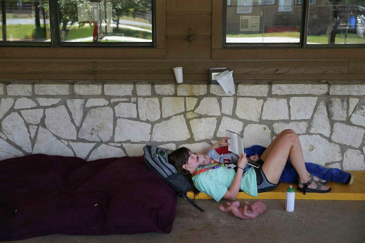 Camp counselor Kayla Smith spends a quiet moment reading a book with camper Jesse Pullin at CAMP Camp in Center Point, Texas on Thursday, Aug. 1, 2019. The camp offers children with special needs and disabilities a traditional summer camp experience and activities like swimming, canoeing, horseback riding and archery. The camp is run by Children's Association for Maximum Potential (CAMP), which is celebrating its 40th anniversary this year. CAMP provides one-on-one supervision for each camper during their weeklong residential sessions. (Kin Man Hui/San Antonio Express-News)