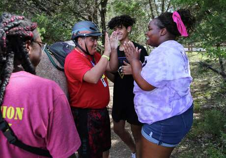 Horseback riding instructor Natalie Crabtree (right) gets a high five from camper William Castaneda after his ride at CAMP Camp in Center in August. The camp, which started in 1979 in rented facilities, is now housed in its own state-of-the-art facility that serves children who are medically fragile and don't often get outdoors as well as children with other conditions and their more typically abled siblings.