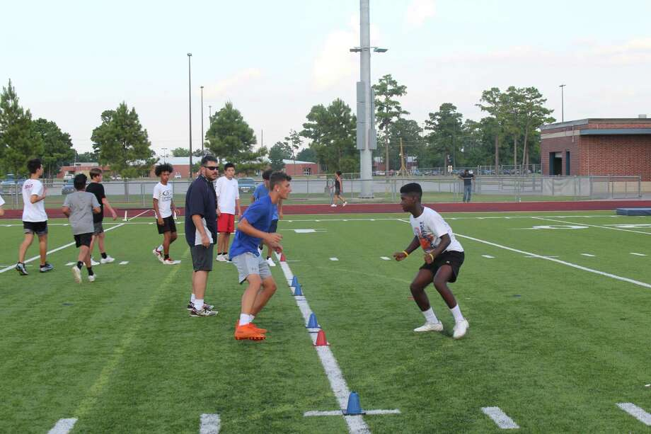 Klein Collins football coach Matt Smith leads campers during a drill at the KC Tiger football camp for incoming 6th-9th graders, July 29-Aug. 1, at Klein Collins High School. Photo: Alvaro Ignacio Montano/staff Photo