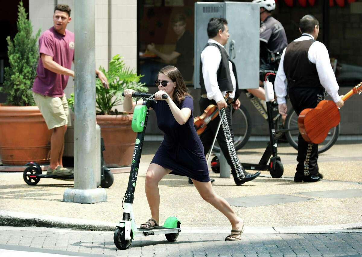 A woman and and man, left, ride scooters across W. Commerce St. on the side walk at Presa St. on Thursday, May, 30, 2019. At the City Counsel meeting city leaders voted to ban riding scooters on sidewalks.