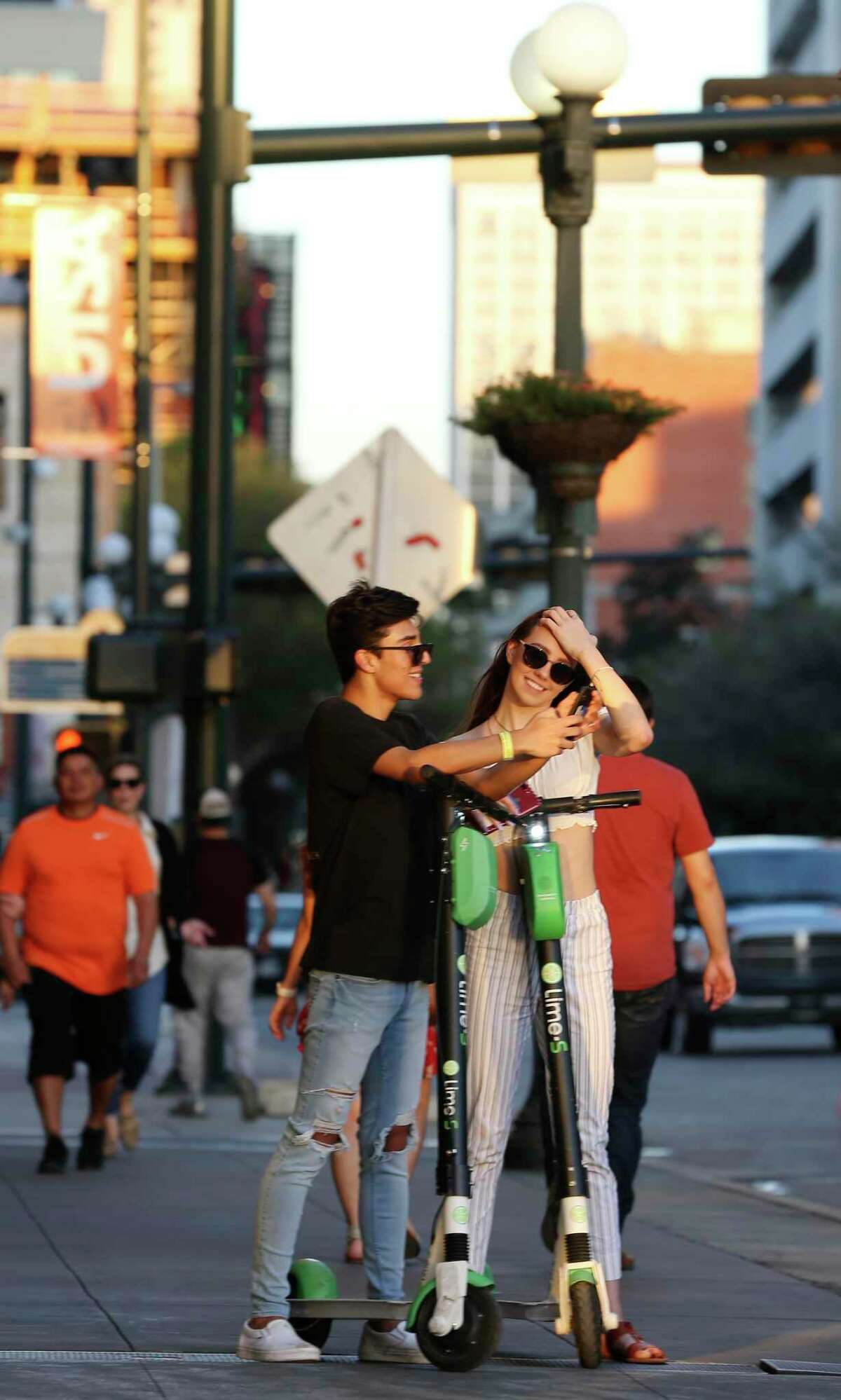 """Trent Newman, 16, and Alexa Sage, 16, stop for a selfie along Commerce Street in downtown San Antonio, Wednesday, March 13, 2019. The scooter rental comes with an 18,404 agreement that straightjackets the customer. The riders had agreed to never sue Lime, take responsibility for all accidents and damage, accept binding arbitration in lieu of any jury trial, limit Lime?•s liability in any event to only $100, waive all participation in class action lawsuits and, among a maze of other promises, affirm that they?•ve not had any drug or alcohol ?'incidents?"""" in the past seven years. They even agreed that Lime has never implied that its ?'equipment will be in good repair.?"""" Virtually every scooter company requires consent to a similar agreement before letting anyone activate one of the city?•s now-ubiquitous dockless vehicles."""