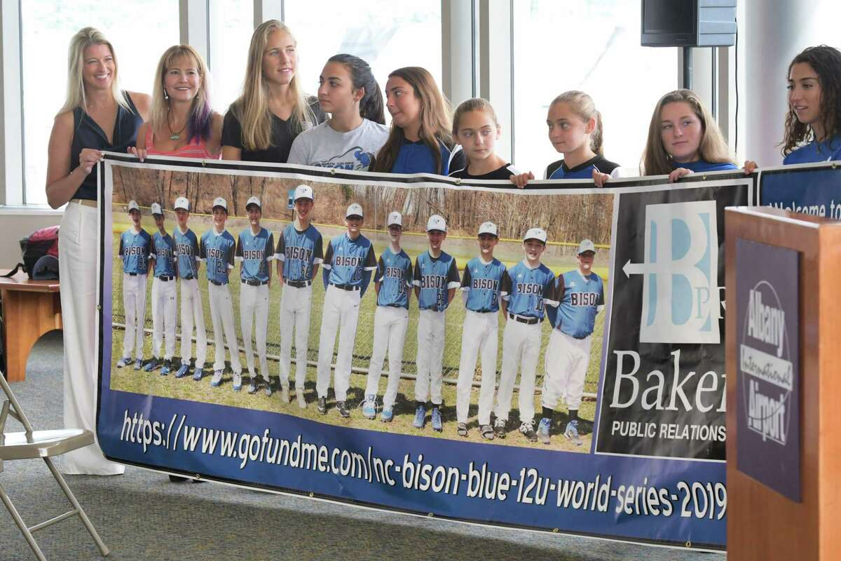 Family of the players with the North Colonie Bison Blue 12u baseball team hold up a banner at the Albany International Airport during a send off for members of the team on Wednesday, July 31, 2019, in Colonie, N.Y. The team was heading to Branson, MO to compete in the Cal Ripken World Series. Last summer the team brought home the Cal Ripken Mid-Atlantic Regional Tournament as eleven year olds and under. That earned them the spot to compete in the Cal Ripken World Series this summer. (Paul Buckowski/Times Union)