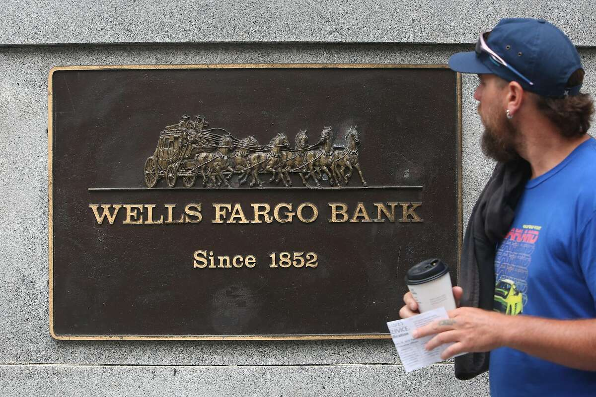 A pedestrian walks past a Wells Fargo bank plaque at 1 Montgomery Street on Tuesday, July 30, 2019 in San Francisco, Calif.
