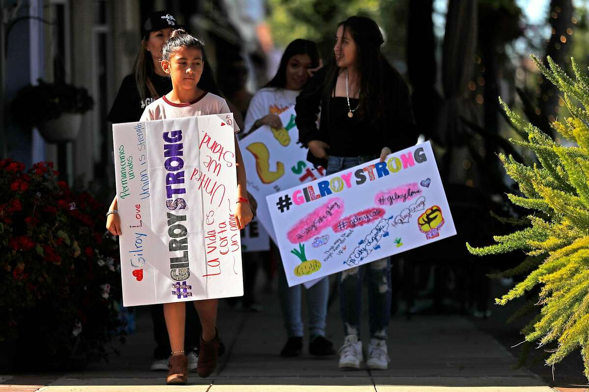 Youth Alliance members led by Alyssa Morales, 12, carries #GilroyStrong signs on Monterey Street in historic downtown Gilroy, Calif., on Thursday, August 1, 2019.