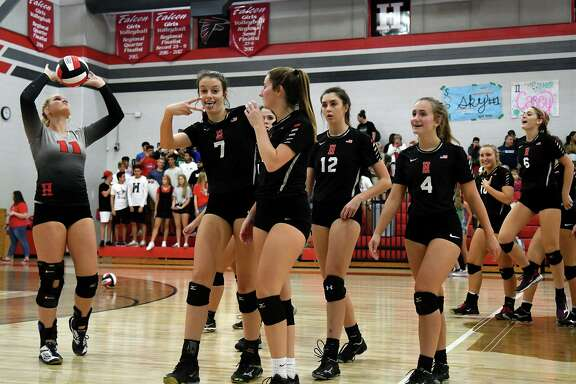 Huffman-Hargrave volleyballers Kylie Willis (7), Saylor Boss (2), and Tina Alley (4) team up in celebration after the Falcons striaght-set win over Livingston at Huffman-Hargrave High School on Sept. 28, 2018.