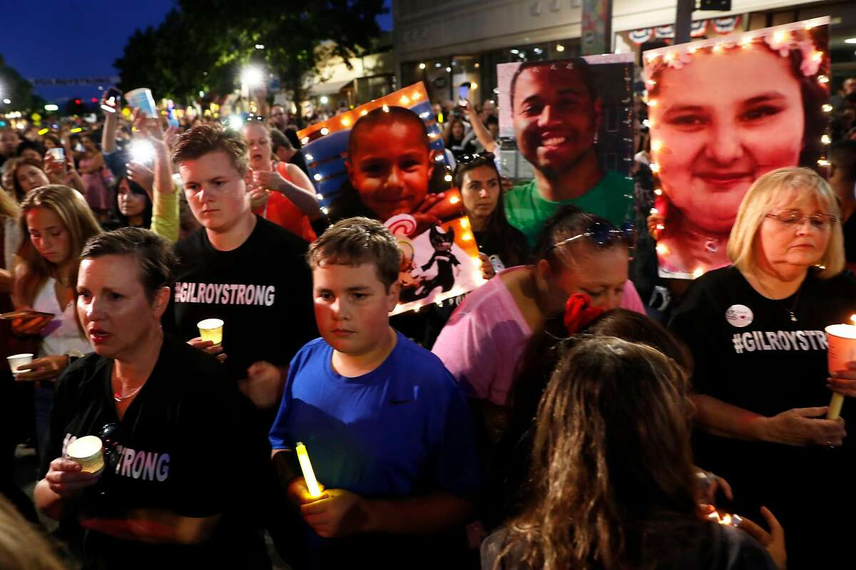 A candelight vigil on Monterey Street in Gilroy, CA, on Aug. 1, 2019, in the wake of the mass shooting at the Gilroy Garlic Festival. The photos of shooting victims, Stephen Romero, 6, Trevor Irby and Keyla Salazar, 13, are being held up.
